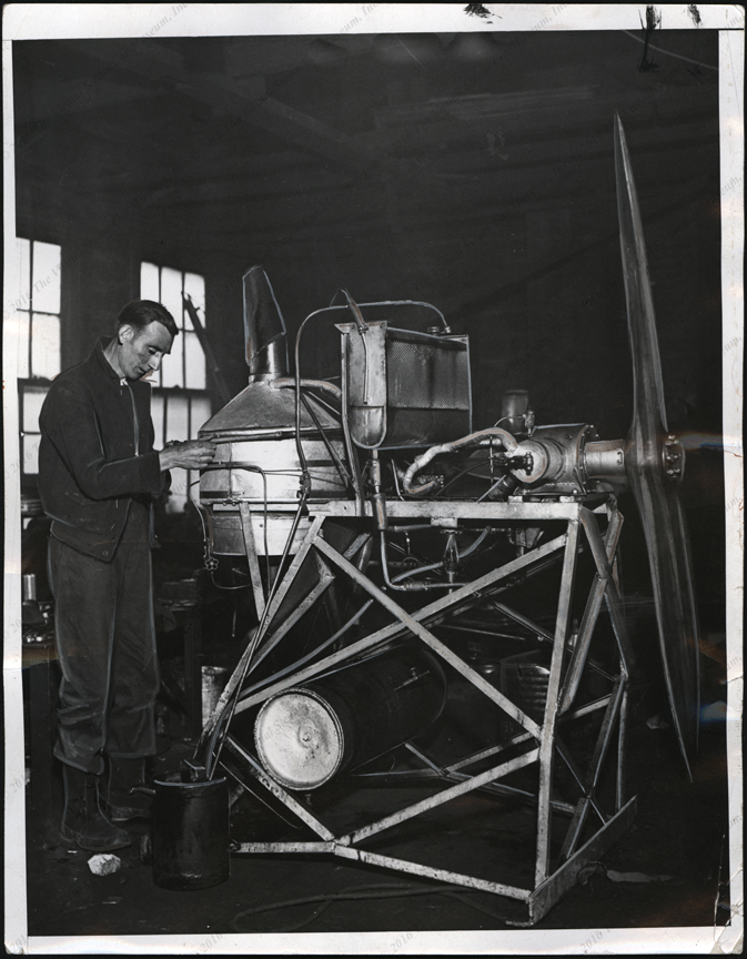 Harold C. Johnston, November 18, 1932, working on his steam areoplane engine, press photo, front